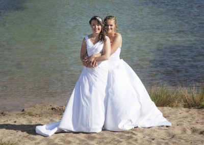 just married happy lesbian couple in white dress embrace near small lake